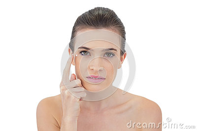 Concentrated natural brown haired model applying face cream