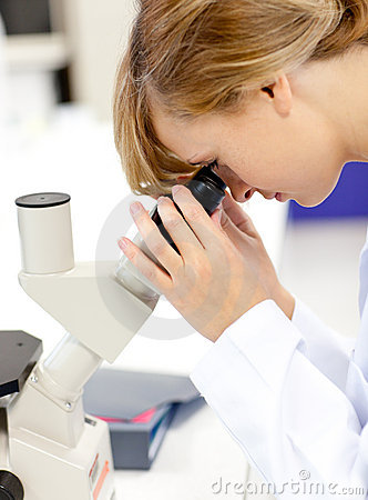 Concentrated scientist looking through microscope
