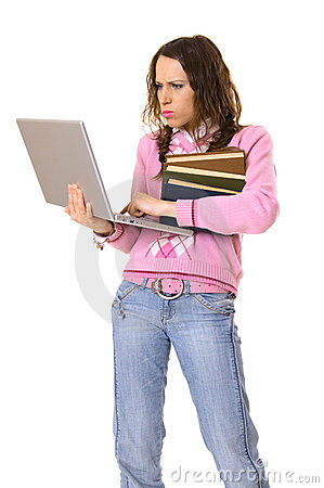 Concentrated woman with laptop and pile of books