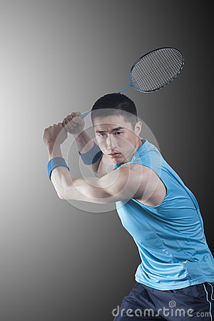 Concentrated Young man playing badminton, racket raised