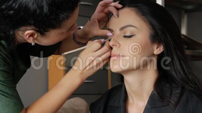 Makeup artist does makeup. Concept of beauty and style. Makeup artist does makeup for a beautiful girl. Close-up of makeup artist master`s hand paints arrows on stock video