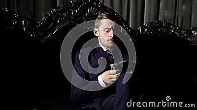 Concept de luxe de la vie L'homme dans le costume, homme d'affaires s'asseyent ? l'arri?re-plan int?rieur de luxe fonc? Mode de v banque de vidéos
