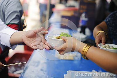 The concept of feeding : The hands of the poor receive food from the hands of the humane : Helping Feed the Poor Stock Photo