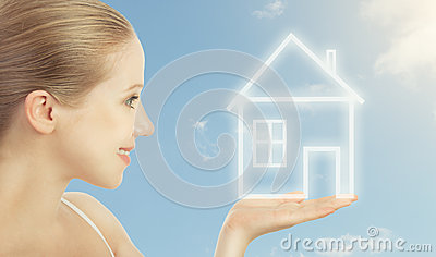 Concept housing. woman holding a house