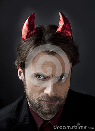 Man in suit with devil horns - concept of cruel boss
