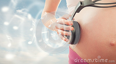 Concept pregnancy and music. belly of pregnant woman and headpho