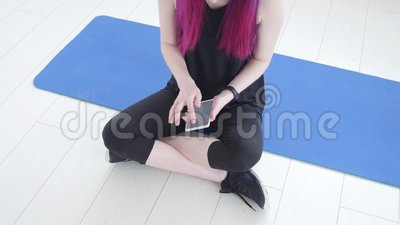 Concept of sport and fitness. Young sportswoman sitting and using fitness tracker and smartphone. On mat in gym stock video footage