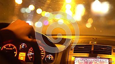 Concept voor het vervoer van chauffeurs: jonge man die 's nachts auto bestuurt , verlichting van auto ' s schijnt in de donkere s stock videobeelden
