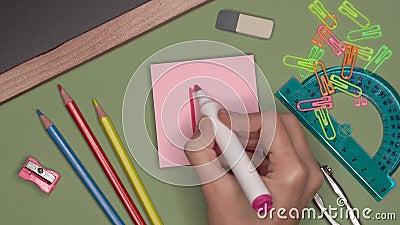 Concepto de la escuela La mano de la mujer que escribe el grado B, buena marca en la libreta almacen de video