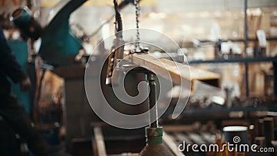Concepto industrial Una grúa de elevación industrial que lleva a cabo un detalle Un hombre controla el proceso metrajes
