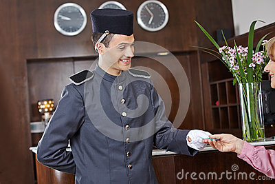 Concergie in hotel giving key card to woman