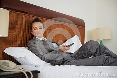 Concerned business woman laying on bed