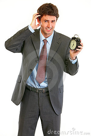 Concerned about time businessman with alarm clock
