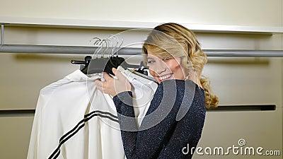 Concetto di acquisto Una ragazza elegante e di moda ha afferrato tutti i vestiti sugli appendiabiti sorridendo alla telecamera, e archivi video