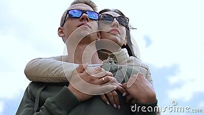Concetto di feste, di vacanza, di amore e di amicizia - coppia sorridente divertendosi sopra il fondo del cielo archivi video