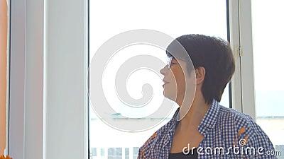 Concetto di ristrutturazione piatta Felice donna di mezza età che dipinge una parete bianca con un rullo di vernice e vernice ara stock footage
