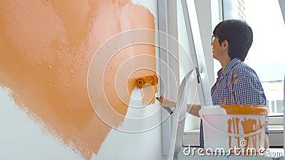 Concetto di ristrutturazione piatta Felice donna di mezza età che dipinge una parete bianca con un rullo di vernice e vernice ara archivi video