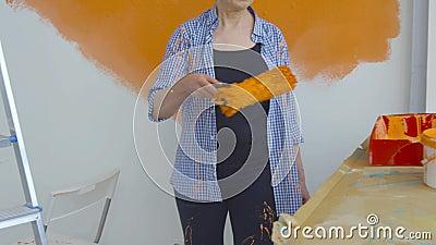 Concetto di ristrutturazione piatta Felice donna di mezza età che dipinge una parete bianca con un rullo di vernice e vernice ara video d archivio