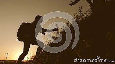 Concetto per avventura e viaggio Un viaggiatore tiene la mano di una donna a un viaggiatore che si arrampica sulla cima della col archivi video