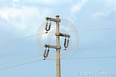 Concrete electrical power line utility pole with ceramic insulators and three connected wires Stock Photo