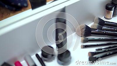 Confección de cosméticos, paleta de los párpados, mascara y pintalabios sobre el espejo retrovisor almacen de metraje de vídeo