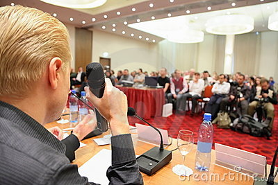 Conference in hall. man with microphone.