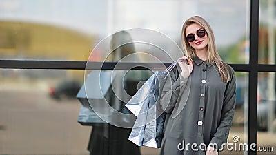 Confiada y relajada, hermosa mujer comercial con bolso de venta de papel sonriente disfrutando del descanso almacen de metraje de vídeo