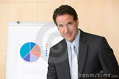 Confident business man with report in background