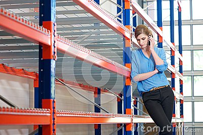 Confident business woman  on cellphone in warehouse