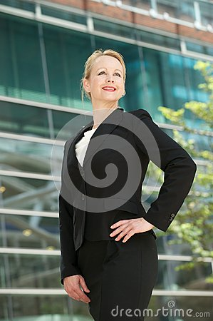 Confident business woman smiling outside office bu