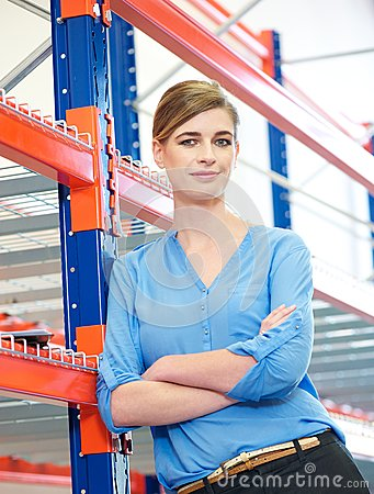 Confident business woman standing in warehouse
