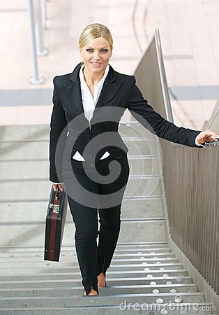Confident business woman walking upstairs with bag