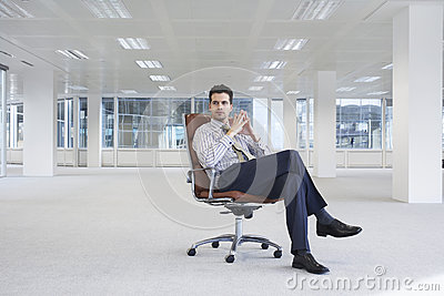 Confident Businessman On Chair In New Office