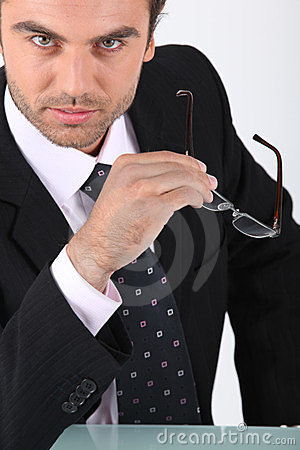 Confident businessman holding glasses