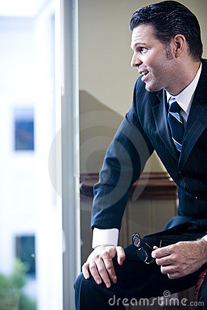 Confident businessman looking out office window