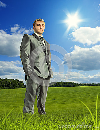 Confident businessman on meadow