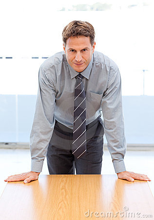 Confident businessman posing leaning on a table