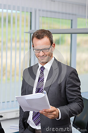 Confident businessman reading a document