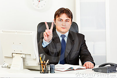 Confident businessman showing victory gesture