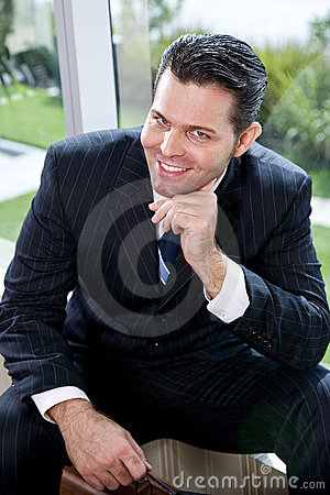 Confident businessman sitting in office by window