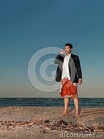 Confident businessman smoking cigar on sea shore