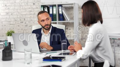 Confident businessman talking with female employee discussing business looking at screen of laptop. Confident male businessman talking with female employee stock footage