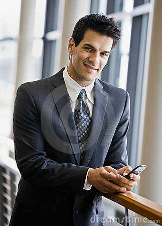 Confident businessman text messaging on cell phone