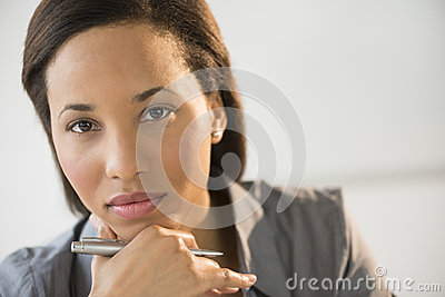 Confident Businesswoman With Hand On Chin