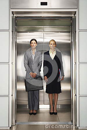 Confident Businesswomen Standing Together In Elevator