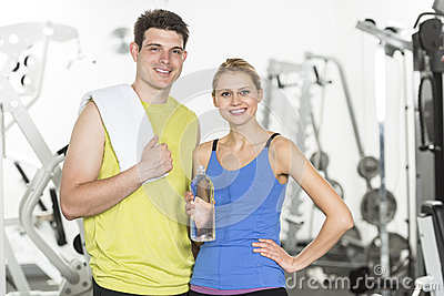 Confident Couple With Towel And Water Bottle In Gym