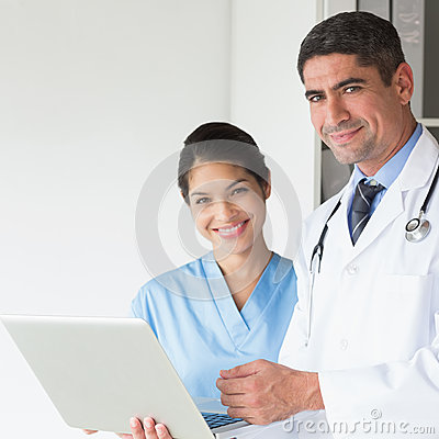 Confident doctor and nurse using laptop