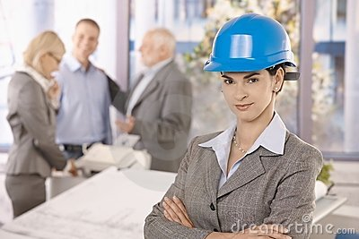 Confident female architect wearing hardhat