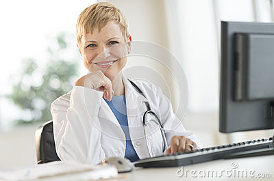 Confident Female Doctor Sitting At Computer Desk
