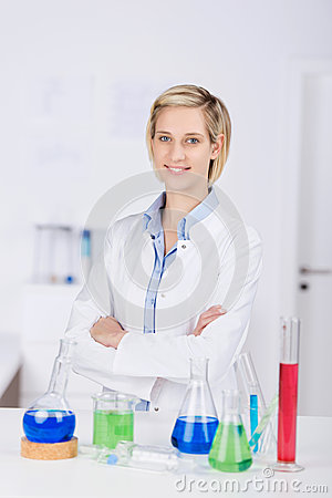 Confident Female Scientist With Arms Crossed Standing At Desk